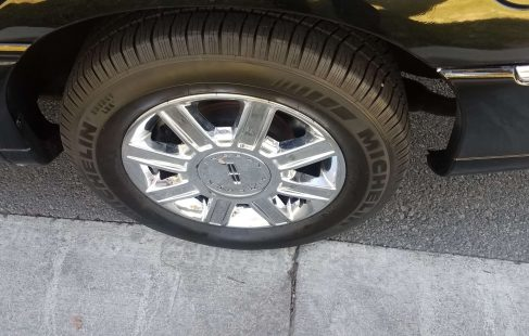 black 120-inch lincoln town car limousine right front tire